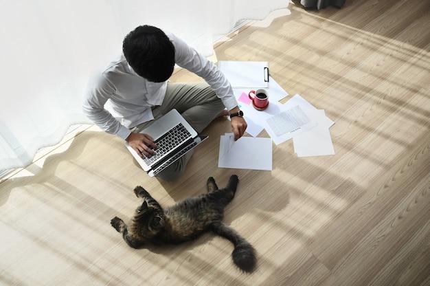 Attraktiver junger mann, der an einem laptop arbeitet, während er mit einer katze auf dem boden in einem bequemen haus sitzt.