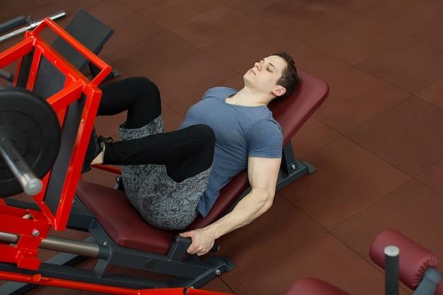 Attraktiver junger mann, der beinpresse auf maschine im fitnessstudio tut