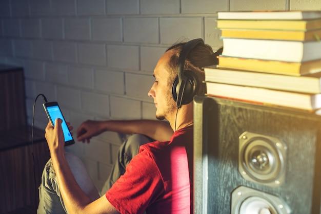 Attraktiver junger mann, der das hörbuch in den kopfhörern hört. konzept der technologieerziehung ein positiver lebensstil