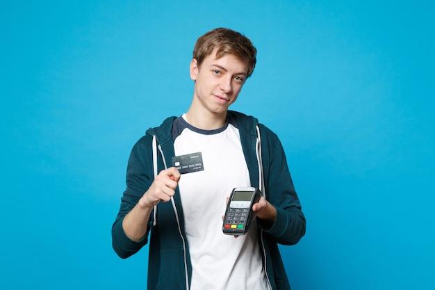Attraktiver junger mann, der drahtloses modernes bankzahlungsterminal hält, um zu verarbeiten, kreditkartenzahlungen einzeln auf blauer wand zu erwerben. menschen aufrichtige emotionen, lifestyle-konzept.