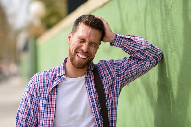 Attraktiver junger mann, der draußen lacht. lifestyle-konzept