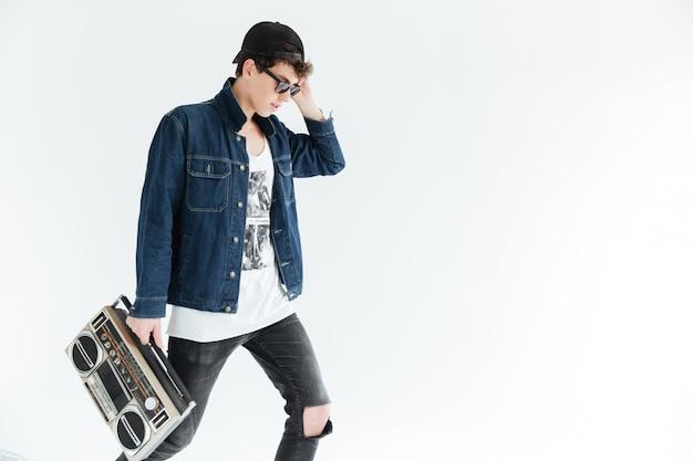 Attraktiver junger mann, der eine brille trägt, die boombox hält.