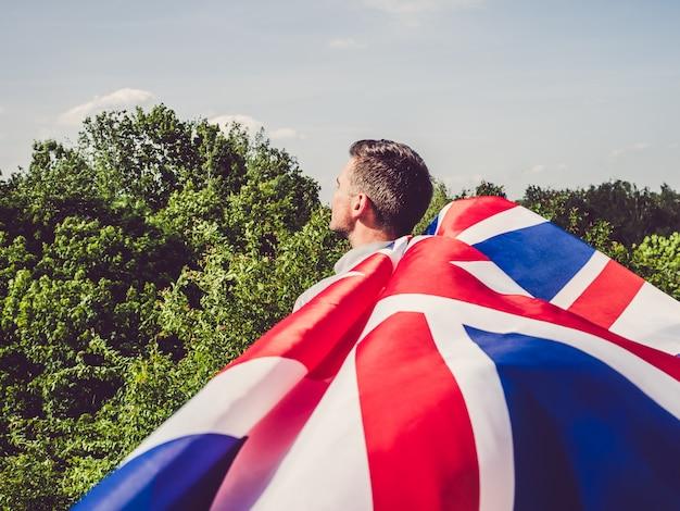 Attraktiver, junger mann, der eine britische flagge wellenartig bewegt