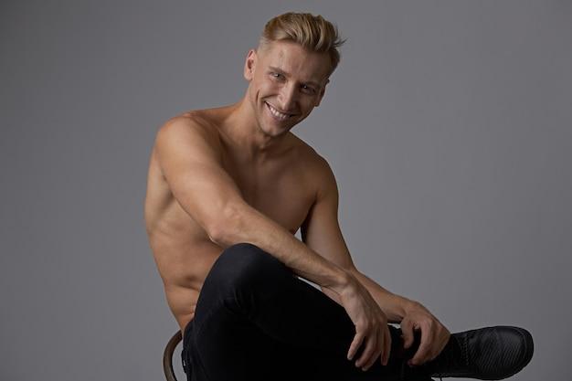 Attraktiver junger mann, der mit dem nackten torso sitzt auf einem stuhl aufwirft