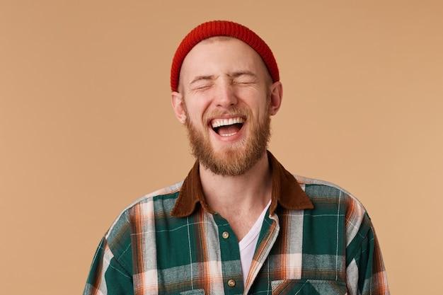 Attraktiver junger mann, der mit geschlossenen freudenaugen lacht