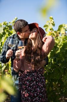 Attraktiver junger mann, der seine schöne freundin in einem weinberg küsst. romantisches paar mit weingläsern.