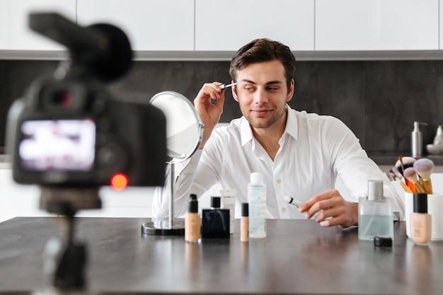 Attraktiver junger mann, der seine videoblogepisode filmt