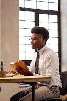 Attraktiver junger mann, der vor dem computer sitzt, während er daran arbeitet