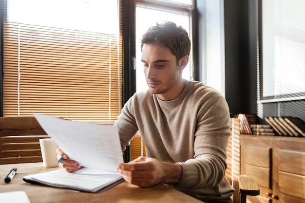 Attraktiver junger mann im büro, der mit dokumenten arbeitet.