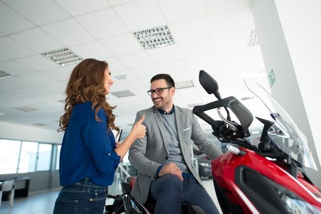 Attraktiver junger mann im händlerausstellungsraum, der neues motorrad kauft