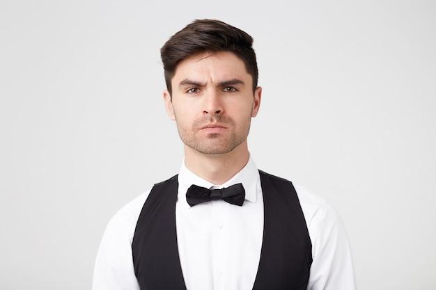 Attraktiver junger mann in einem anzug mit einem schmetterling schaut aufmerksam. ernsthafter gesammelter mann sieht gerade aus