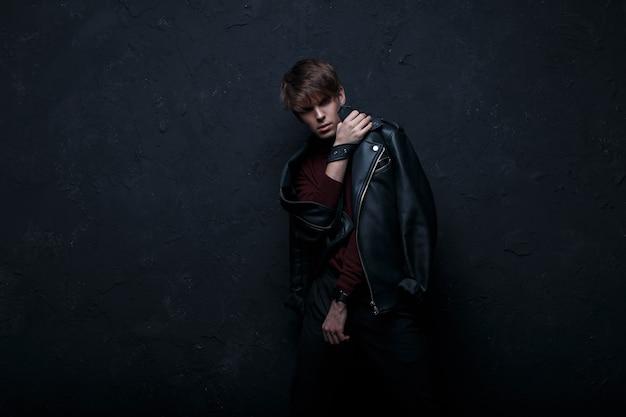 Attraktiver junger mann in einer schwarzen lederjacke im retro-stil mit burgunderrotem golf und trendigen schwarzen jeans steht in einem dunklen studio an einer schwarzen wand. netter kerl