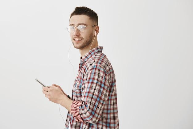 Attraktiver junger mann mit brille posiert mit seinem telefon und kopfhörern