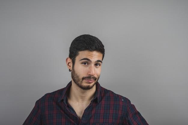 Attraktiver junger mann mit dem bart, der geradeaus, junger mann glücklich schaut