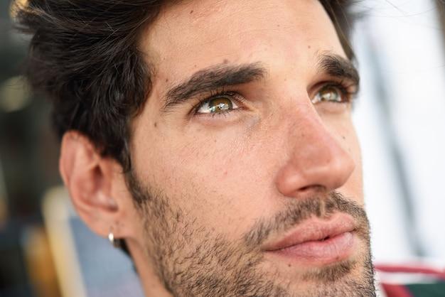 Attraktiver junger mann mit dem dunklen haar und moderner frisur, die draußen zufällige kleidung trägt