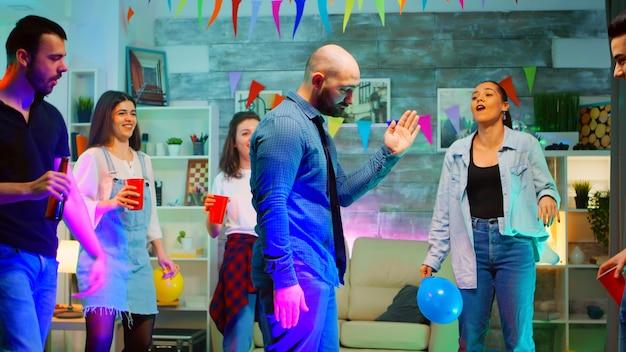Attraktiver junger mann mit glatze, der robotertanzbewegungen macht, während er mit seinen freunden in einem raum voller neonlichter, discokugel und cooler stimmung feiert