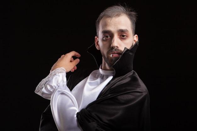 Attraktiver junger mann mit gruseliger haltung und gekleidet wie dracula für halloween. mann im dracula-kostüm mit ernstem gesicht.