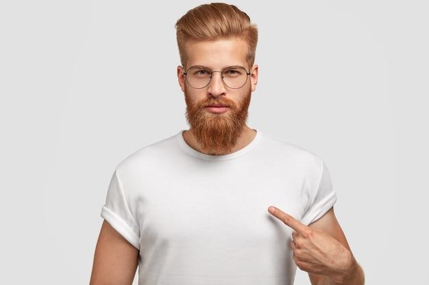 Attraktiver junger mann mit rotem haarschnitt und bart, zeigt auf leeres t-shirt