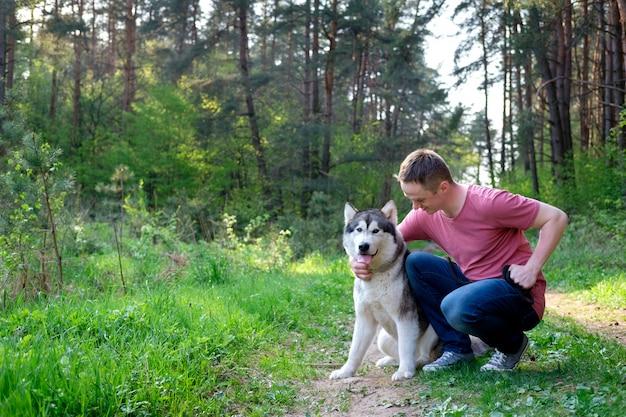 Attraktiver junger mann mit seinem hundemalamute auf einem weg im wald