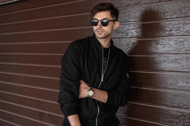 Attraktiver junger mann mit stilvoller frisur in modischer schwarzer kleidung in trendiger dunkler sonnenbrille ruht in der nähe einer braunen vintage holzwand auf der straße. urbaner typ. amerikanischer stil.