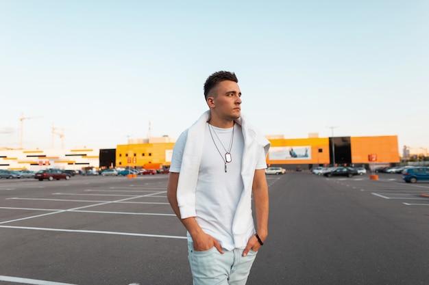 Attraktiver junger mann mit trendiger frisur in einem weißen vintage-t-shirt mit einem sweatshirt in modischen blauen jeans posiert in der stadt an einem sommertag. hübsches städtisches kerlmodell im freien.
