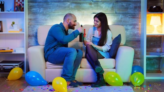 Attraktiver junger mann und schöne frau treffpunkt auf einer party mit guter musik. alkohol trinken.