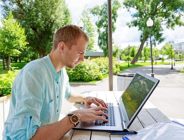 Attraktiver junger mannschüler, der laptop außerhalb benutzt