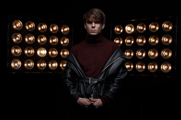 Attraktiver junger stilvoller mann in einer lederjacke im burgunderfarbenen stilvollen golf steht in einem dunklen studio vor dem hintergrund der leuchtend orangefarbenen vintage-pfoten der lichter. netter modestar kerl