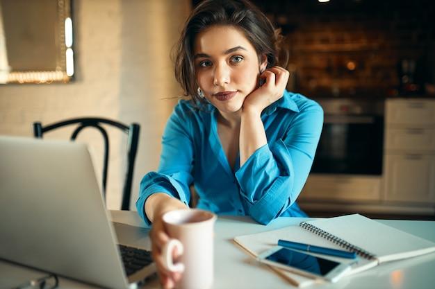 Attraktiver junger weiblicher angestellter, der laptop für fernarbeit sitzt, sitzt am schreibtisch mit handy und becher, trinkt kaffee, macht bericht. nettes studentenmädchen, das online auf tragbarem computer zu hause studiert