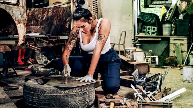 Attraktiver junger weiblicher mechanischer arbeiter, der ein altes auto in der alten garage repariert.