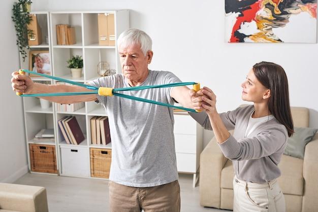 Attraktiver junger weiblicher persönlicher trainer, der dem älteren mann übung mit gummi erklärt, um seine wirbelsäulenmuskeln zu stärken