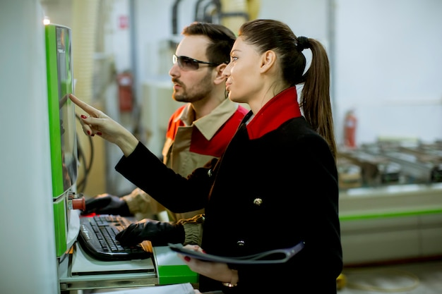 Attraktiver junger weiblicher techniker, der inspektion an der produktionsabteilung der anlage durchführt