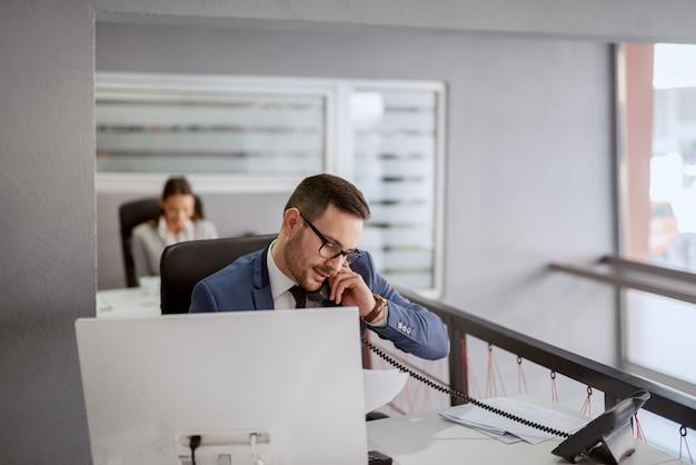 Attraktiver kaukasischer geschäftsmann in formeller kleidung, der an seinem arbeitsplatz sitzt und einen anruf hat, während er papierkram betrachtet. wenn sie größe erreichen wollen, hören sie auf, um erlaubnis zu bitten.