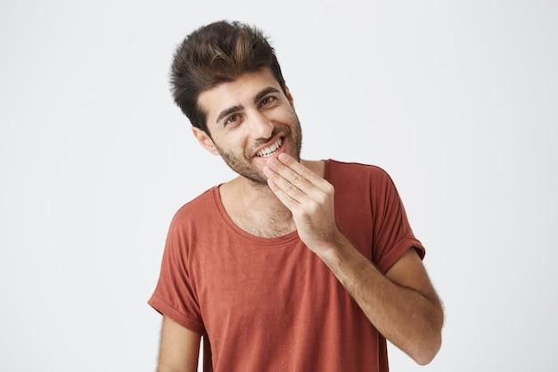 Attraktiver kaukasischer junger mann, der angenehm aussieht. fröhlich und lächelnd zeigt er, dass seine weißen zähne gute laune haben, nachdem er gute nachrichten erhalten hat