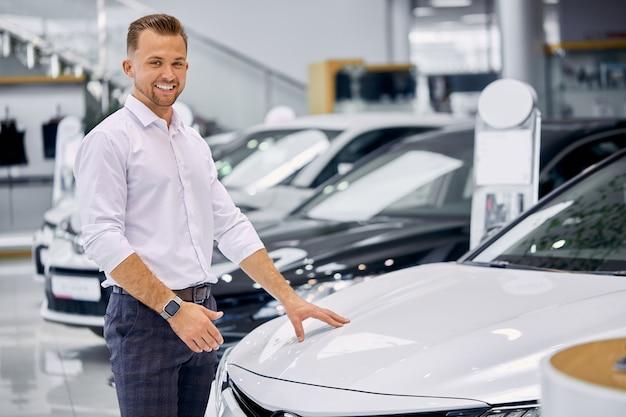 Attraktiver kaukasischer kundenmann steht neben weißem luxusauto im autohaus