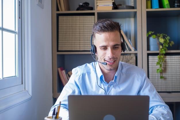 Attraktiver kaukasischer mann sitzt im homeoffice-raum mit headset und nimmt mit laptop an einem pädagogischen webinar teil. videoanruf-event mit kunden oder persönlicher chat mit freund aus der ferne konzept