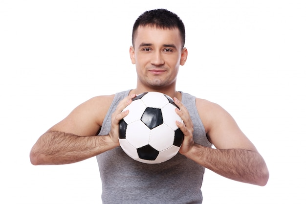 Attraktiver kerl, der fußball hält