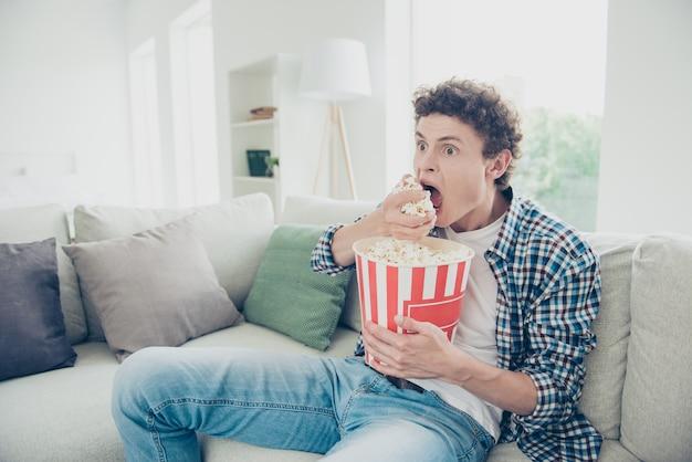 Attraktiver kerl, der lässiges sitzendes sofa zu hause trägt, das popcorn isst