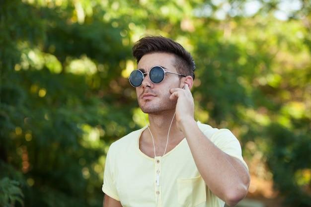 Attraktiver kerl im park mit hörender musik der sonnenbrille