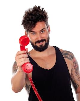 Attraktiver kerl mit einem alten roten telefon