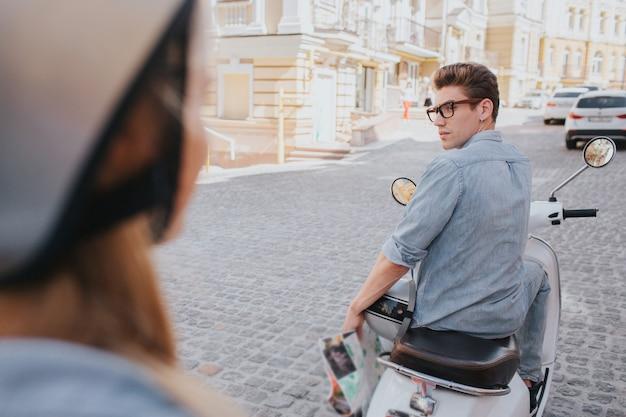 Attraktiver kerl sitzt auf motorrad und betrachtet zurück frau
