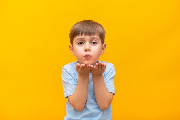 Attraktiver kleiner junge, der einen kuss bläst, liebe für seine freundin demonstriert oder sich aus der ferne verabschiedet, isoliert auf gelbem studiohintergrund.