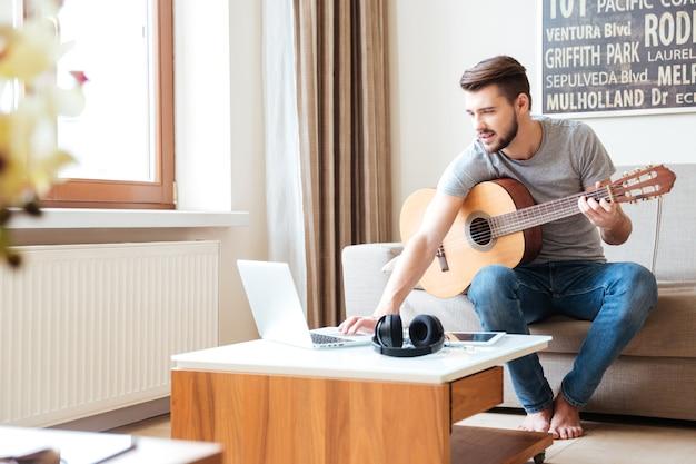 Attraktiver konzentrierter junger mann mit laptop, der auf sofa sitzt und gitarre spielt