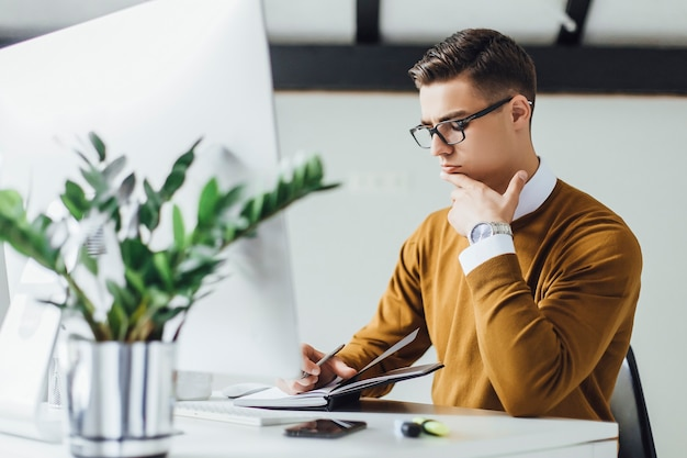 Attraktiver, kreativer geschäftsmann mit laptop-computer, der notizen im büro schreibt