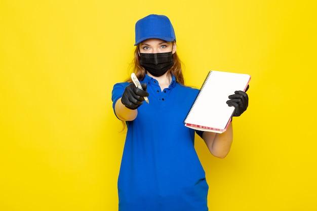 Attraktiver kurier der weiblichen vorderansicht in der blauen kappe des blauen poloshirts und der jeans in der schwarzen schutzmaske der schwarzen handschuhe, die stift und notizbuch auf dem gelben hintergrundlebensmittelservicejob hält