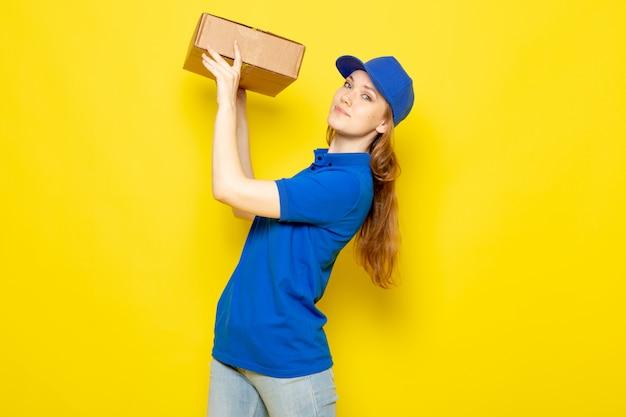 Attraktiver kurier der weiblichen vorderansicht in der blauen kappe des blauen poloshirts und in den jeans, die paket halten, das auf dem gelben hintergrundlebensmittelservicejob lächelt