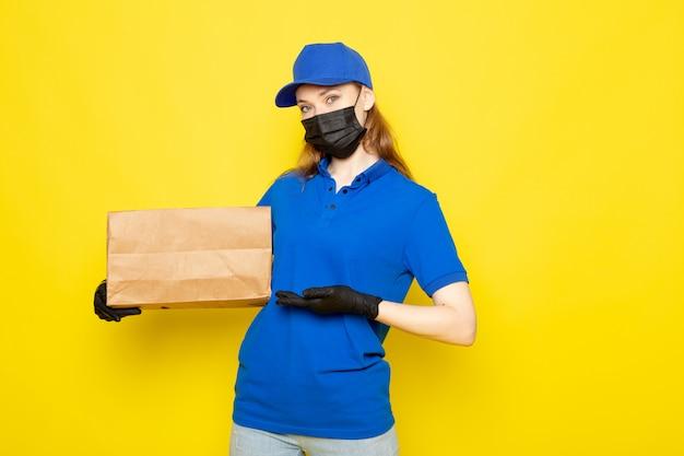 Attraktiver kurier der weiblichen vorderansicht in der blauen kappe des blauen poloshirts und in der jeans, die paket in der schwarzen schutzmaske der schwarzen handschuhe auf dem gelben hintergrundlebensmittelservicejob hält