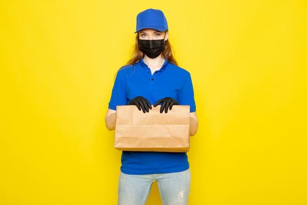 Attraktiver kurier der weiblichen vorderansicht in der blauen kappe des blauen poloshirts und in der jeans, die paket in der schwarzen schutzmaske der schwarzen handschuhe halten, die auf dem gelben hintergrundlebensmittelservicejob aufwirft