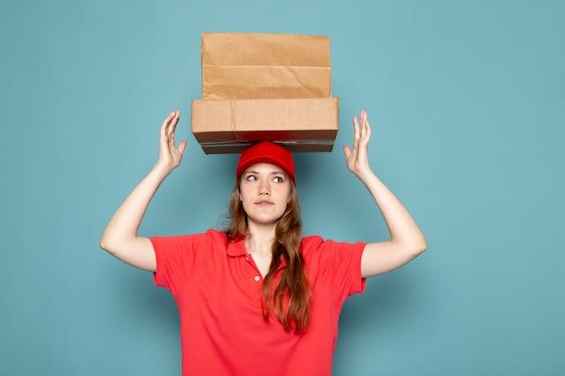 Attraktiver kurier der weiblichen vorderansicht in der roten kappe des roten poloshirts, die braune pakete über ihrem kopf hält, der auf dem blauen hintergrundlebensmittelservicejob aufwirft