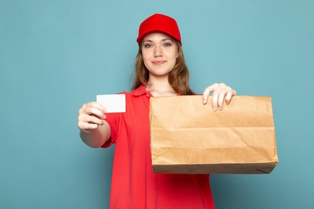 Attraktiver kurier der weiblichen vorderansicht in der roten kappe des roten poloshirts und in den jeans, die paket- und weiße karte halten, die lächelnd auf dem blauen hintergrundlebensmittelservicejob aufwirft